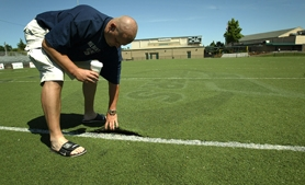 by: Jaime Valdez, APART AT THE SEAMS — Stace Shillitto, of Tigard High's security personnel and assistant coach for both football and baseball, pulls up on the turf at Tigard High's stadium field last summer before crews came out to glue the surface back down.