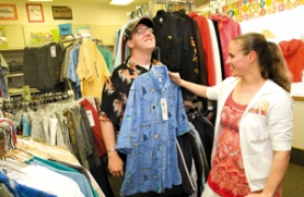 by: John Klicker, Centennial Transition Center student Kevin Klinger, 21, gets help from Melissa Cooley, 20, as she practices her sales skills at the Closet to Closet shop in the newly remodeled Centennial Transition Center on Tuesday, April 15, during the center's open house. Closet to Closet, not open to the public, is for needy students inside the Centennial District who get vouchers to use at the store for clothing and other items they may need. Klinger works as a groundskeeper for the center and Melissa Cooley works at an internship with Jo-Ann Fabrics and Crafts store in Gresham.