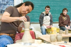 by: John Klicker, Nobu Kosai, renowned potter from Sapporo, Japan, demonstrates his style of throwing pots Wednesday, April 16, to Mt. Hood Community College ceramics students Cody Taylor, center, and Sam Morise, right, two of 20 students gathered at the college ceramics studio. Kosai will be showing his work with 24 members of the Hokkaido Pottery Society at the Ceramic Showcase to be held at the Oregon Convention Center in Portland from April 25-27.