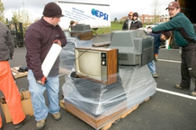 by: John Klicker, Gresham city workers Brenden Hoberg, left, and Bob Brown, right, wrap a pallet full of TVs as they volunteer during the Earth Day Celebration at Gresham City Hall on Saturday, April 19. Residents of Gresham and Wood Village brought in old electronics, fluorescent light bulbs and computers for recycling.