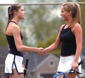 by: DAN BROOD, WELL DONE — Tualatin High School junior Anna Hildebran (left) and senior Maddie Bachhuber congratulate each other following their victory in No. 1 doubles play in the Timberwolves league match with Tigard.