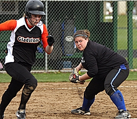by: MILES VANCE, DIAMOND GIRLS — Valley Catholic senior first baseman Emily Becker (above) scoops up a Gladstone bunt during her team's 2-1 10-inning non-league home loss to the Gladiators last Wednesday afternoon.