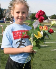 by: Contributed photo, A NEW VOLUNTEER – Jaelyn Clopfil, one of the youngest volunteers from last year's Oregon's Run for the Roses, celebrates after the fundraising event.