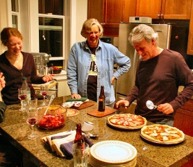 "by: Todd Sargent, Lara Utman and Patsy Steimer supervise Dan Steigerwald, as he slices the local pesto to combine with the locally-produced tomato sauce for the mozzarella pizza, at the ""Green Team"" March potluck supper in Woodstock."