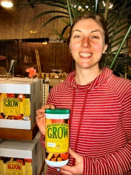 "by: Rita A. Leonard, At ""Everybody's Garden Center"", sales associate Katie holds a sample of the company's top-selling plant nutrient, ""Golden Grow"", manufactured there for over 20 years."