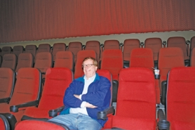 by: Cecelia Haack, Chuck Nakvasil kicks back in one of the seven theaters in his new complex, which opens Friday. The $8 million facility represents the latest in theater technology and the culmination of a lifelong dream for Nakvasil, who grew up in Scappoose.