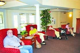 by: Cecelia Haack, Dave Olsen, who recently moved in; Mara Wolpshin, a visitor; resident Loranne Anderson; and resident Bertha Randolph enjoy the newly redecorated lobby.