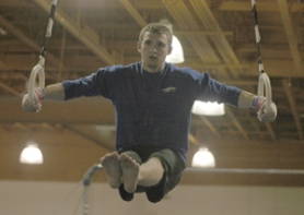 by: David Ball, Gresham senior Ben DeRemer works out on the rings during a recent practice session at Top Flyte gym in Troutdale.
