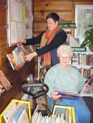 by: Ellen Spitaleri, Barbara-Lee Orloff, the director of the Booktique, arranges books on a rack, while Carol Kay looks at a children's book taken from the yellow wagon.