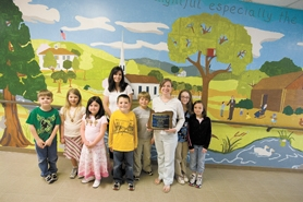 by: Chase Allgood, Parent volunteers Tyla Young (in back) and Kimberly Howell (holding plaque) stand with Harvey Clarke Elementary School students Ty Perini, Alaura Sullivan, Olivia Frederick, Casey Young, Patrick McGee, Megan Howell and Chandler Young in front of a gigantic history-oriented mural that was completed last fall at the Forest Grove grade school.