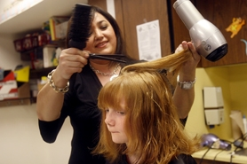 by: Jonathan House, TRESS STRESS — Kathleen Chapman gets her hair chopped and styled by Soheila Rashidi at Errol Hassell Elementary School's Locks of Love event Saturday during the school's carnival. Participants donated their hair to make wigs for children who have lost their own.