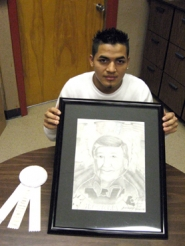 by: Ray Pitz, GIFTED ARTIST — Jesus Trejo displays a portrait of Cesar Chavez that he sketched for an art contest last month.