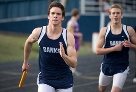 by: Chase Allgood, Banks senior Brad Markham takes off on the final leg of the 4x400 meter relay last Thursday after taking the handoff from his brother, Brock.