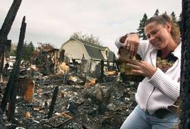 by: Jaime Valdez, WHAT REMAINS – Kim Williams sifts through the remains of her home off of Robbins Road just outside of Tualatin. She picked up a bundle of paper not completely destroyed by the April 4 fire that gutted her home. Not surprisingly, the surviving paperwork turned out to be a bill.