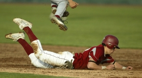 by: JAIME VALDEZ, SAFE AT SECOND — Tualatin High School senior Mitchell Lambson dives safely to second base, while a Forest Grove player jumps over him, during Tualatin's 10-3 win over the Vikings.