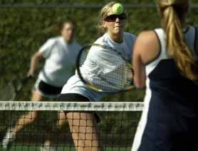 by: JAIME VALDEZ, NET WORK — Sherwood's Katie Patterson, playing in front of doubles partner Melany Boulton gets her racquet on the ball in Monday's match at Wilsonville. Patterson and Boulton scored a 6-4, 6-4 victory.
