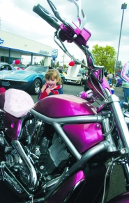 by: marcus hathcock, A little girl enjoys the hot pink motorcycle on display at the 2006 Suburban Car Show.