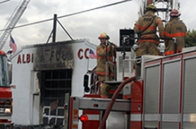 by: Jonathan House, Portland firefighters battled a blaze Tuesday afternoon that destroyed the empty Albina Fuel Co. building on Northeast 33rd Avenue. Smoke from the blaze billowed over Interstate 84 during rush-hour traffic.