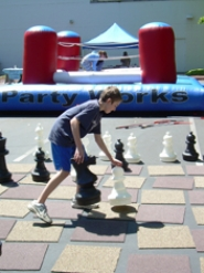 by: Kristen Forbes, Tommy Viggiano, 13,  makes his move in a giant chess game at the West End Building Monday in Lake Oswego as part of the Tween and Teen Summer Kick-Off party.