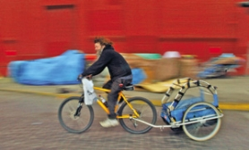 by: L.E. BASKOW, Richard Grijalva rides his bicycle with an attached trailer under the Morrison Bridge. More homeless people are adopting this mode of transportation, which allows for greater mobility and the ability to haul their possessions. Donations of bikes and trailers are needed.