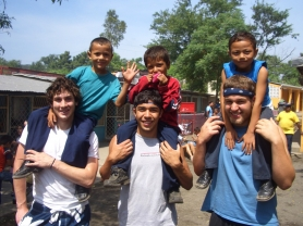 by: , From left, Matt Murray, Matt Brooks and Conor Liguore give rides to three children in La Chureca during a family day festival at the school.