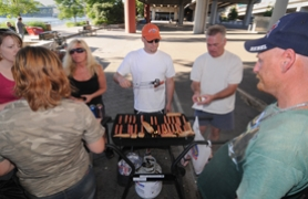 by: Vern Uyetake, 1987 Lakeridge graduate Travis Vanstaverren, at grill, spends a couple nights a week under the Hawthorne bridge in Portland, grilling hot dogs, for members of the homeless community who have spread the word of Vanstaverren's work. Some begin showing up hours before the dinner time.