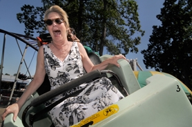 by: Vern Uyetake, Oaks Park Senior Manager Mary Beth Coffey goes for a quick ride on the carnival's small roller coaster.