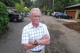by: VERN UYETAKE, Doug Oliphant stands in front of his Allen Road home. The street, and an easement there, will see heavy construction when the city of Lake Oswego begins building its main sewer system in Oswego Lake in 2009.