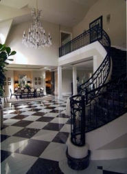 by: Vern Uyetake, The vaulted entry to the home has a sweeping staircase, marble checkerboard floor and light fixutres from the 1930s.