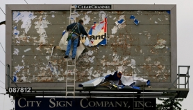 by: L.E. BASKOW, A worker from the City Sign Co. Inc. peels away an old billboard ad in preparation for applying a new one along Southeast Stark Street near 146th Avenue.