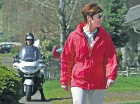 by: L.E. BASKOW, Sharon White, the city's traffic-safety program specialist, sports a bright red jacket and light-colored slacks as she makes her way again along the crosswalk at Southeast 122nd Avenue and Main Street during an enforcement detail with the Portland Police.