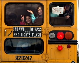 by: L.E. BASKOW, Students from Portland's Atkinson Elementary School wave goodbye from the back of their bus as they leave the Oregon state Capitol following a rally last month, organized by the education advocacy group Stand for Children.