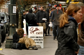 by: L.E. BASKOW, A man sleeps atop his bags along Southwest Ninth Avenue in downtown Portland as the lunch crowd streams by. A downtown business owner and homeless advocate offer differing views on a controversial ordinance that bans sitting or lying on the city's sidewalks.