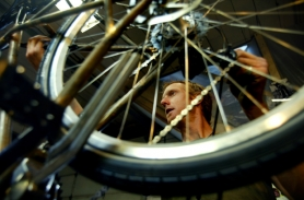"by: L.E. BASKOW, Portland bicycle builder Joseph Ahearne (above) adjusts the brakes on his current project from within the workshop he shares with Mitch Prior. Both builders will participate in Oregon Manifest's ""Constructors' Design Challenge."""