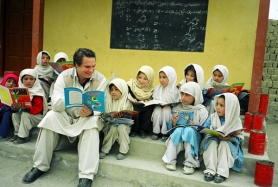 by: Courtesy of Central Asia Institute, Greg Mortenson, who will give a lecture at Concordia University on Oct. 21, is shown here reading to Gultori schoolchildren in Pakistan, at a school he helped build.