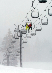 by: COURTESY OF CHRISTOPHER ONSTOTT, Two snowboarders ride the Mount Hood Express chair at the Meadows in near whiteout conditions as heavy snowfall blankets the mountain on Tuesday. Meadows opened Nov. 11, the earliest opening in 15 years.