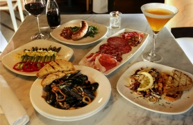 by: L.E. BASKOW, Bar Mingo, an extension of Caffe Mingo next door, features a long list of small dishes, including (clockwise from front) mussels, asparagus, sausage, salumi and Insalata di Mare, pared with a glass of chianti and an Emily's Sidecar.