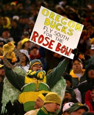 by: L.E. BASKOW, A Ducks fan, complete with bird wings and giant silver medallion, cheers on his team during the Dec. 3 Civil War game. Such enthusiasm is only increasing as Ducks fans look forward to the Rose Bowl.