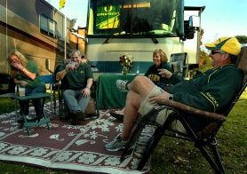 by: L.E. BASKOW, Debby Branford (left) and her husband Steve laugh with friends Margie and Marv Staggs while recalling past bowl games they've attended. The couples were some of the first to arrive earlier Monday by RV and parked at Brookside Park just south of the Rose Bowl.