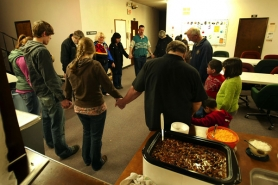 by: L.E. BASKOW, Volunteers and homeless guests take part in an optional prayer before sharing dinner at the Metro Church of Christ in Gresham, one of the Portland-area churches that participates in the Human Solutions Daybreak Shelter program.