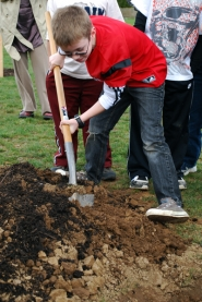 "by: Geoff Pursinger, Luke Netzlof, a second-grader at Mary Woodward Elementary School, helps plant a tree April 8 as part of the city's ""100 Trees"" project."