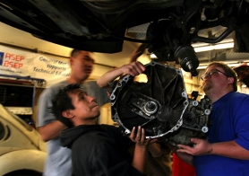 by: Tribune File Photo, Students team up to lift a transmission into place in Benson Polytechnic High School's automotive shop in 2008. The  proposed high school redesign plan would convert Benson to a two-year, half-day vocational program starting in 2011. The school board votes on the plan in June.
