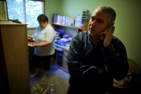 by: Christopher Onstott, Mitch Besser waits on hold to find out about his unemployment benefit status as his wife Diana organizes the home office. Besser, who was featured in a July 22 Tribune story, worked for a software company that moved its operations to China, laying off most of its Oregon workers.