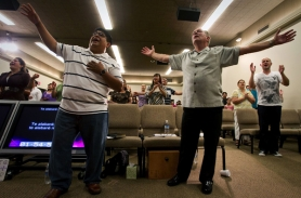 by: Christopher Onstott, Carlos Hernandez (left) and Jack Louman sing in the front row of  City Bible Church in Tigard during a Sunday service, which is translated into Spanish.