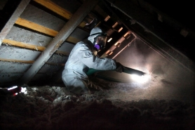 by: JONATHAN HOUSE, Ted Snider of EcoTech LLC, one of the contractors for Clean Energy Works, blows insulation into the attic of a customer's home.