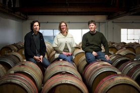 by: CHRISTOPHER ONSTOTT, (From left) John Grochau, Anne Hubatch and Vincent Fritzsche sit atop of barrels of wine stored in Grochau's Northwest winery.