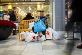 by: CHRISTOPHER ONSTOTT, Ray Gough is lost in a sea of shopping bags at Lloyd Center while he waits for his family to rescue him.