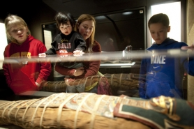 "by: CHRISTOPHER ONSTOTT Brianna Wolterman (center) holds Kanoa Buckley, 2, as they look at ""Annie"" (short for Anonymous), an unidentified girl whose body was purportedly pulled from the Nile River and mummified — on display at OMSI's"