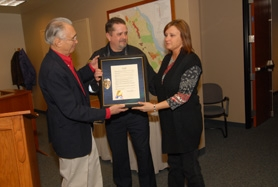 by: VERN UYETAKE Mayor John Kovash and West Linn Police Chief Terry Timeus  present Satter's wife, Rene, with a plaque.