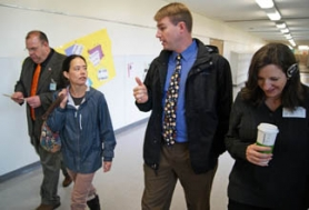 by: Tyler Graf WALKING — St. Helens Middle School Interim Principal Tim Olietti (center) walks the halls of his school flanked by school visitors, including County Commissioner Henry Heimuller (left).
